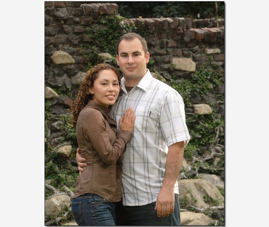 HIspanic-American couple casual pose in front of stonewall