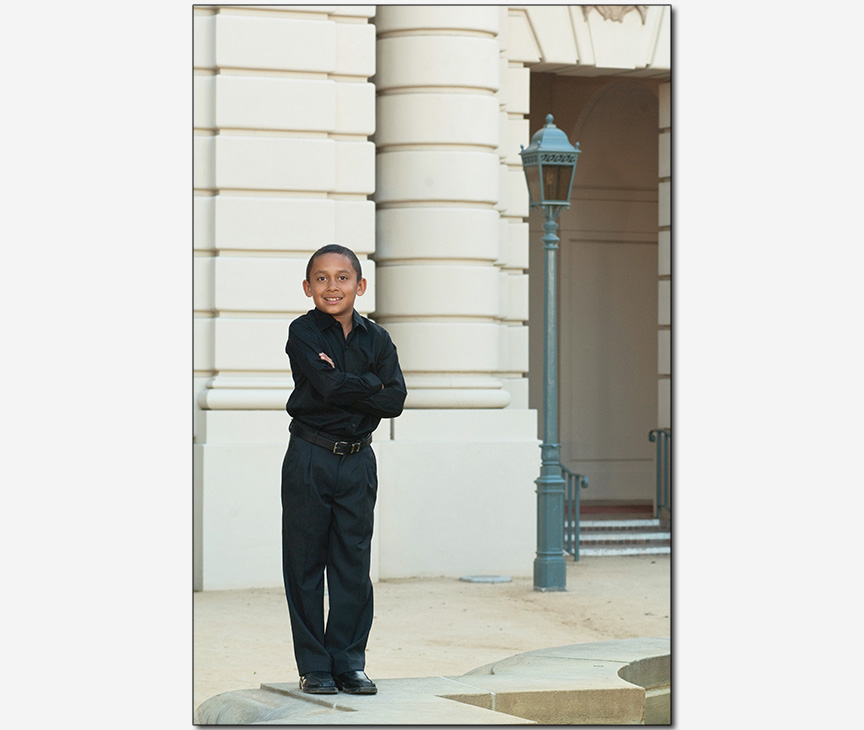 boy posed on fountain with retro building in background