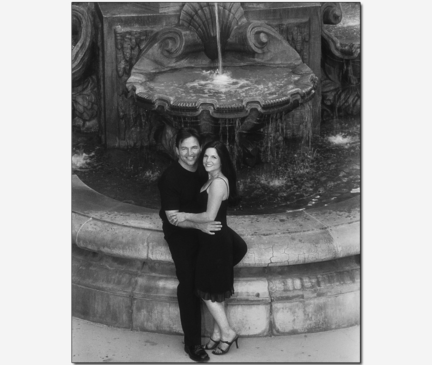 couple smiling on a fountain