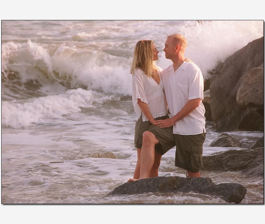 couple un-nerved waves crashing behind | engagement photos