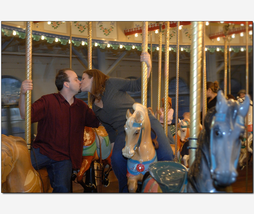 engaged couple kissing on a carousel
