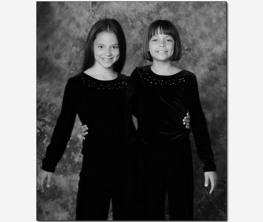 two pre-teen sisters arm in arm